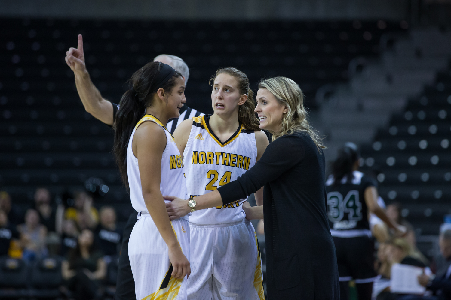 Grace White (1) and Molly Glick (24) talk to Head Coach Camryn Whitaker during a free throw in the game against Cleveland State.
