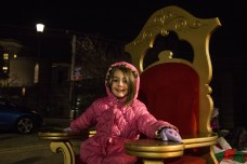 Five-year-old resident Nadia Maybee poses on Santa's chair as she waits for his arrival at Observatory Hill's inaugural Light Up Night. Photo credit: Chloe Jakiela