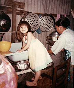 A five-year-old Aishah helping with the dishes in her grandfather's house in Ipoh