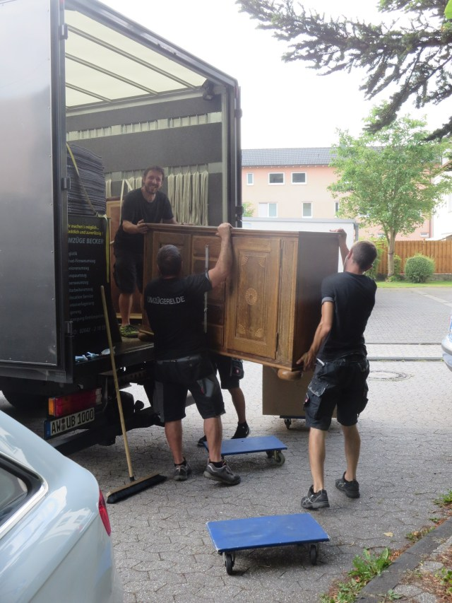 The guys loading the bottom of an ancient cupboard into the truck.