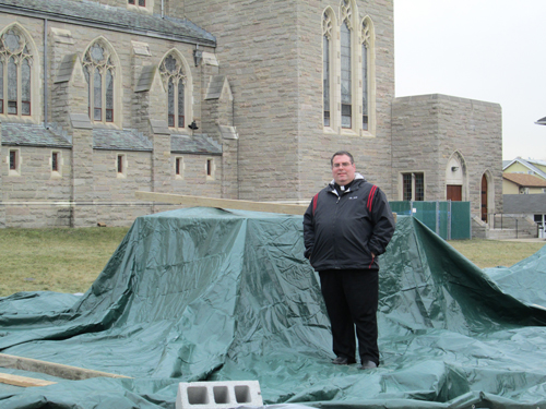 Photo by Ron LeirThe Rev. Joseph Mancini stands by tarpaulin-covered pedestal where Four Chaplains monument will rest.