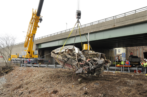 What remains of long-abandoned boat that was blocking Passaic River is removed from waterway.
