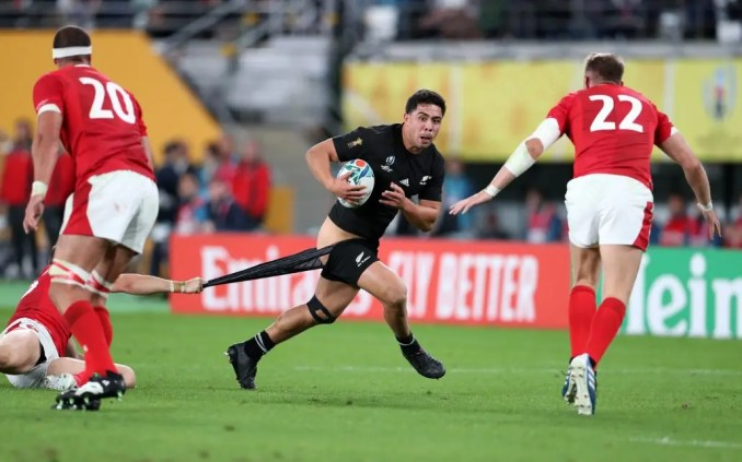 New Zealand centre Anton Leinert-Brown gets his shorts pulled down by the despairing tackle of Wales full-back Hallam Amos in the 3rd/4th place play-off. Image: Fotosport/David Gibson
