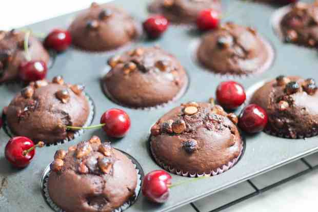 Chocolate Cherry Muffins in muffin tin with scattered cherries