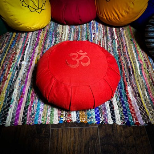 Red meditation cushion with om sanskrit symbol on colorful rug for sale at the om shoppe in sarasota fl