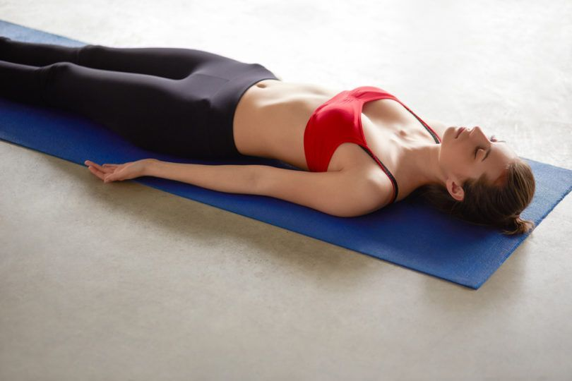 Young attractive woman in yoga outfit rests on the floor of the gym room in savasana corpse pose after yoga class