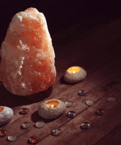 Himalayan salt lamp and candles on table against dark background