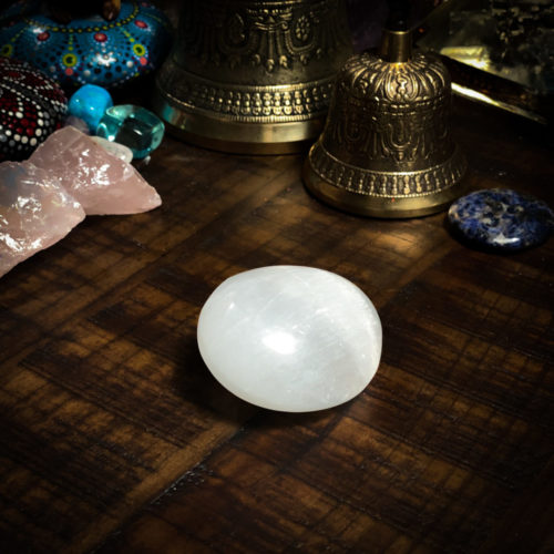 Selenite Palm Stone with bells behind it on a wooden table at the om shoppe