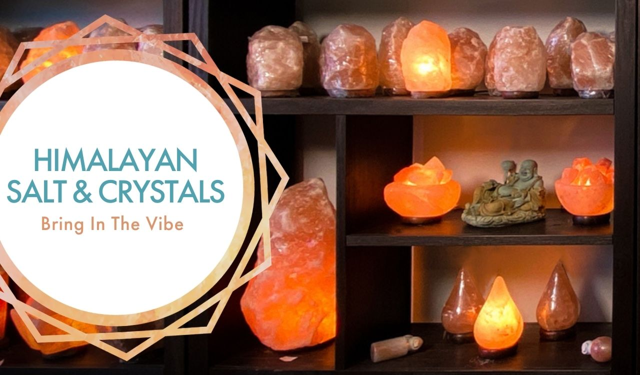 Himalayan Salt & Crystals: Bring In The Vibe. Backdrop is a wall of shalves with various salt lamps on display