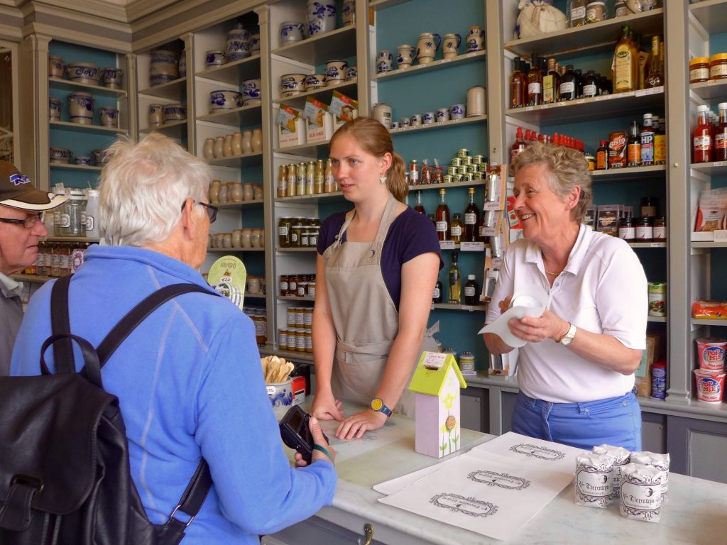 Shop owners assisting customers in a mustard shop in Ghent, Belgium. - Open Suitcase