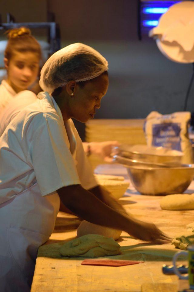 A woman kneading bread in a Stellenbosch bakery-Stellenbosch wine tours are fun after exploring downtown.