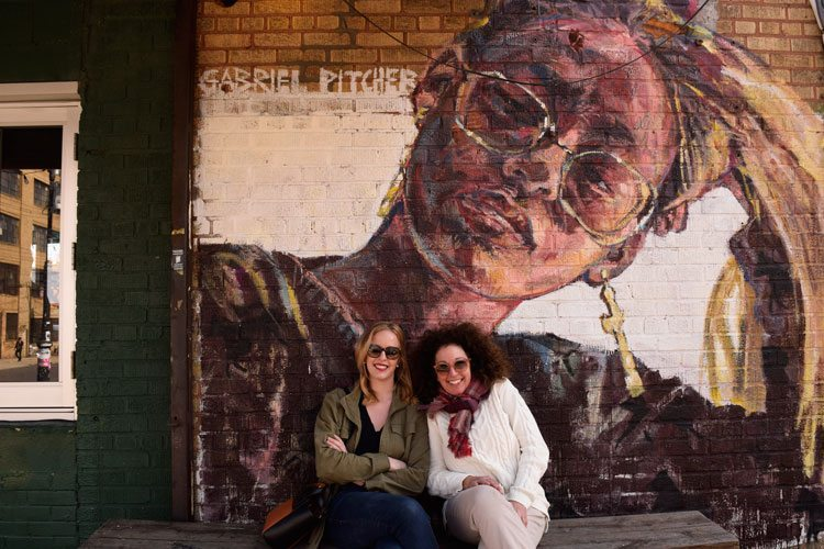 Mother and daughter posing in front of a mural in Bushwick, Brooklyn.
