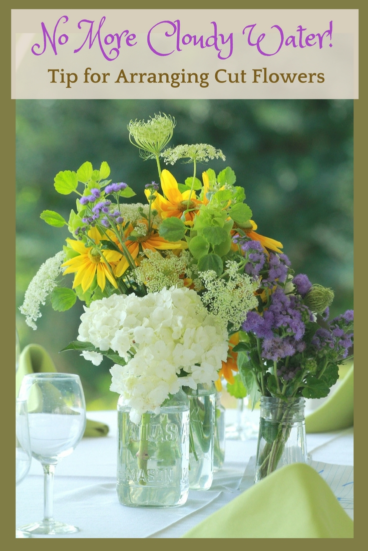 Cut summer flowers in a mason jar on a table outside.
