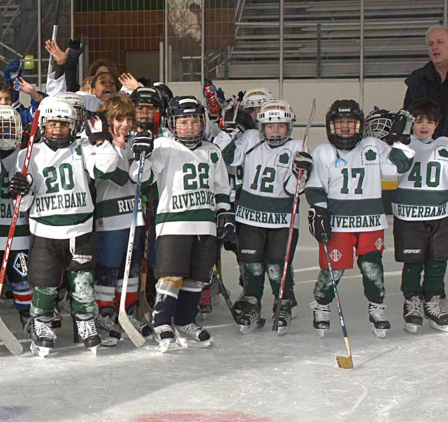 Group of children in hockey gear on the ice at Riverbank State Park in NYC