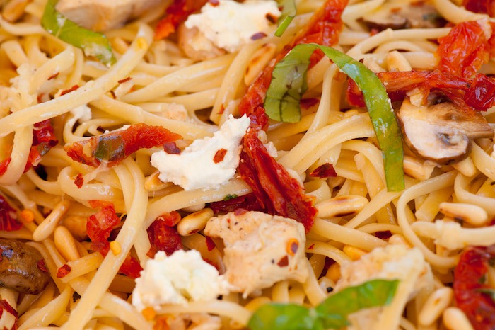 A close up of Linguini with Chicken and Goat Cheese garnished with basil chiffonade