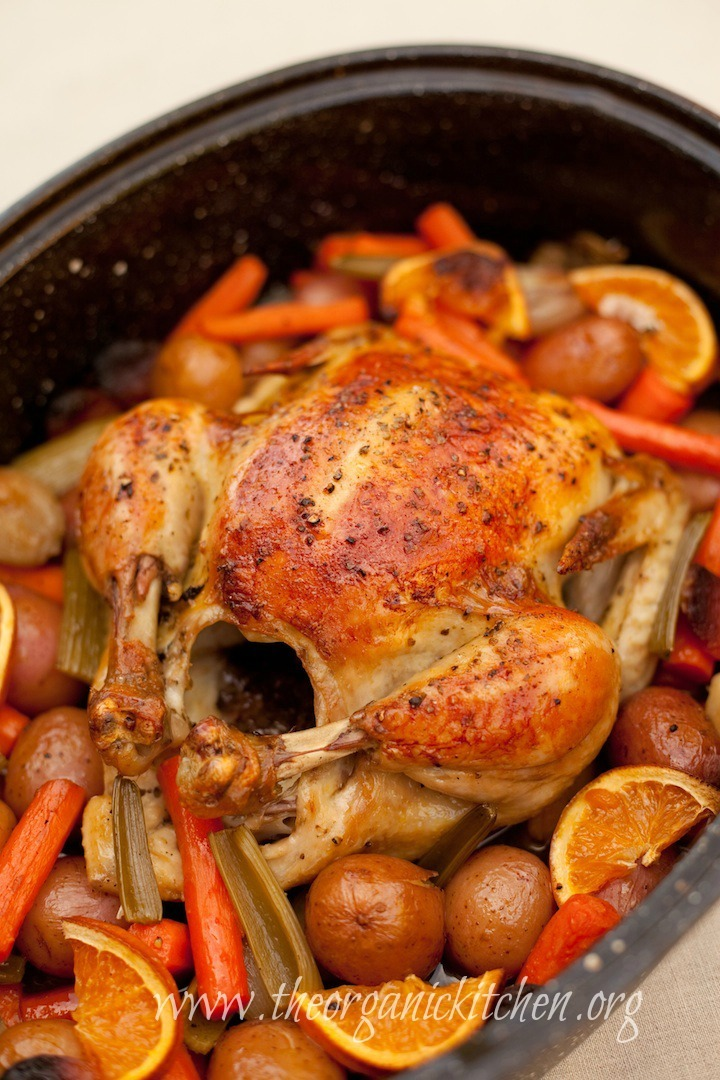 Roasted Apricot Chicken in a black roasting pan surrounded by carrots, potatoes and orange slices