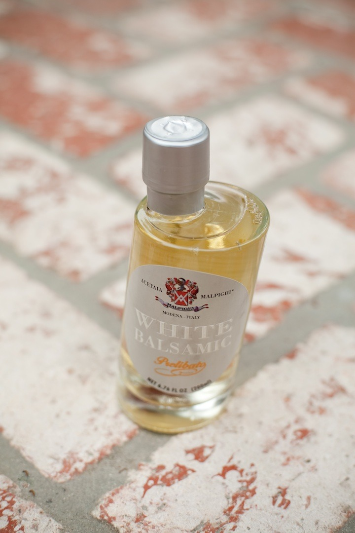 A bottle of white balsamic vinegar set on bricks