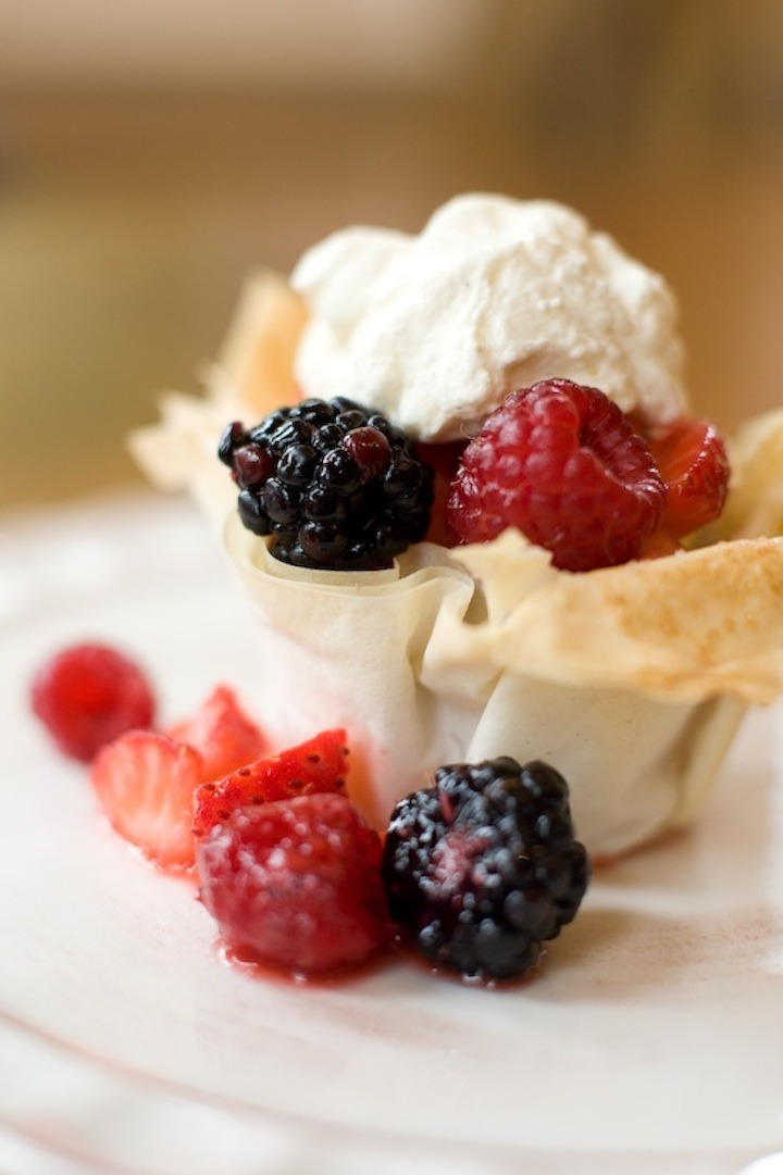 Berries in a Pastry Basket topped with whipped cream on white plate