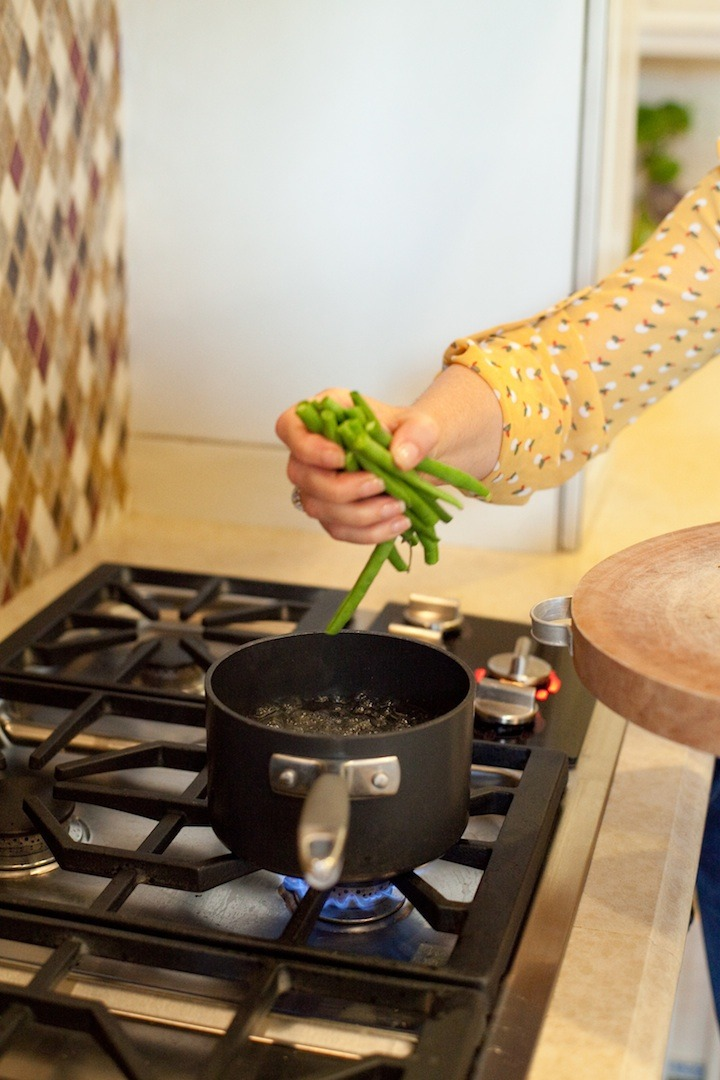 I females right hand dropping green beans into a pot of boiling water, to demonstrate how to make simple blanched green beans