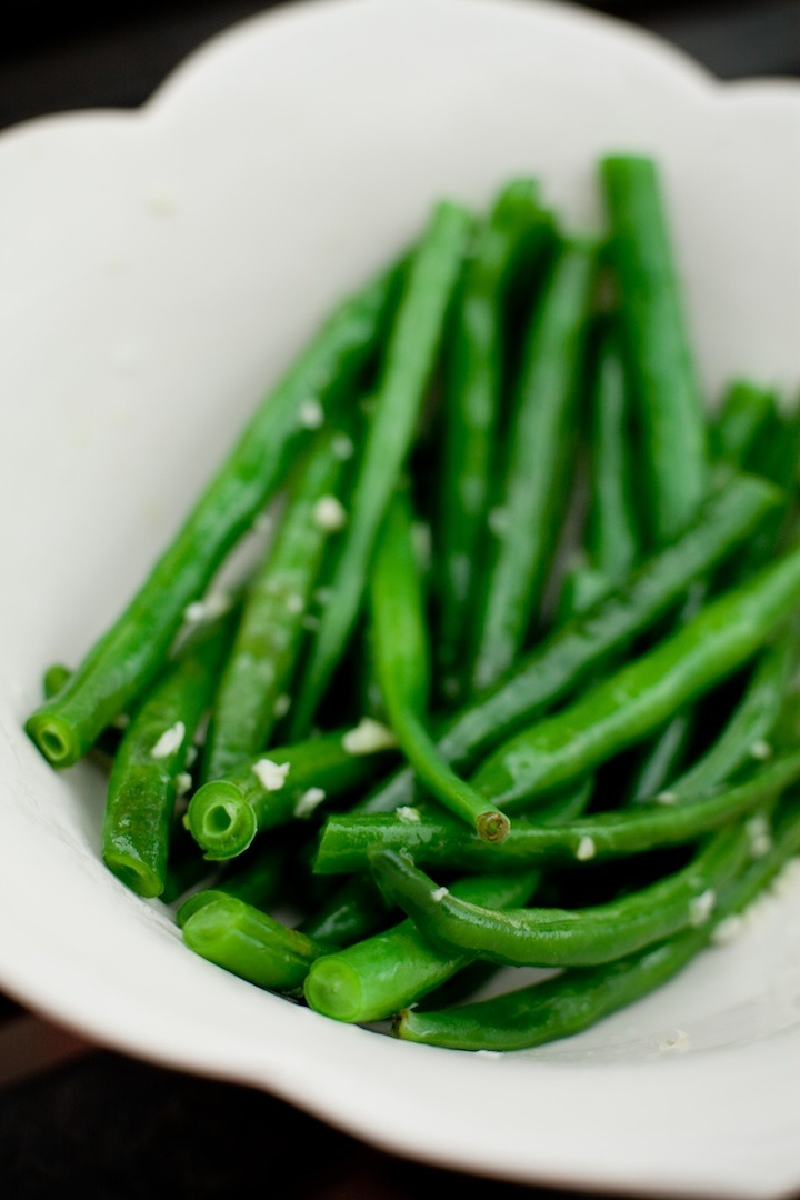 A close up photo of simple blanched green beans in a white bowl on black background