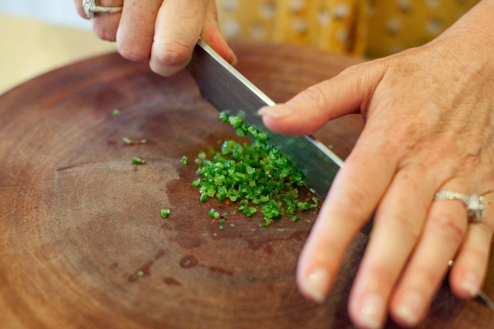 a females hands holding a knife demonstrating how to chop a hot chili pepper on a cutting board
