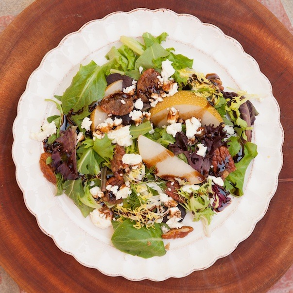 Greens with Asian Pears and Fig Balsamic on a white plate set on a wood cutting board