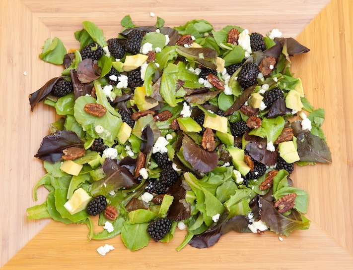 A platter filled with baby lettuce, blackberries, feta cheese , avocado and caramelized nuts