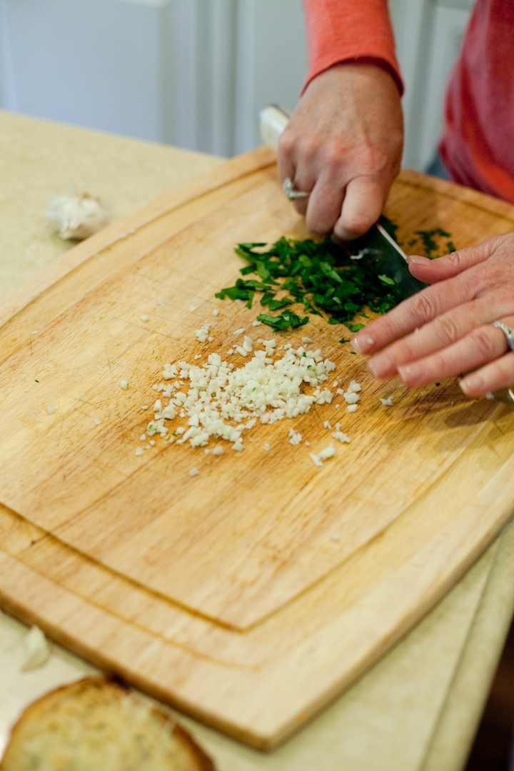 A woman holding a knife and chopping parsley and garlic to use as a  garnish for Chicken Piccata from The Organic Kitchen