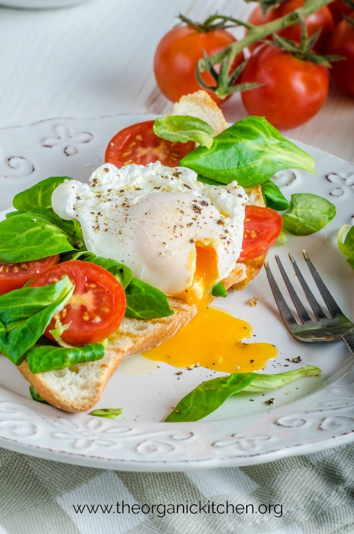 A white plate with Poached Eggs and Veggies on Toast with tomatoes in the background