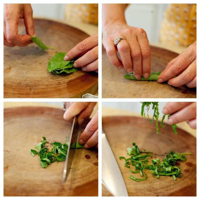 A woman's hands demonstrating how to make a basil chiffonade for use in Heirloom Tomato Linguini