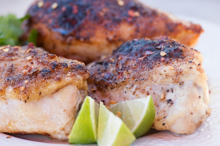 A close up of three pieces of spicy lime chicken  with lime wedges on white plate