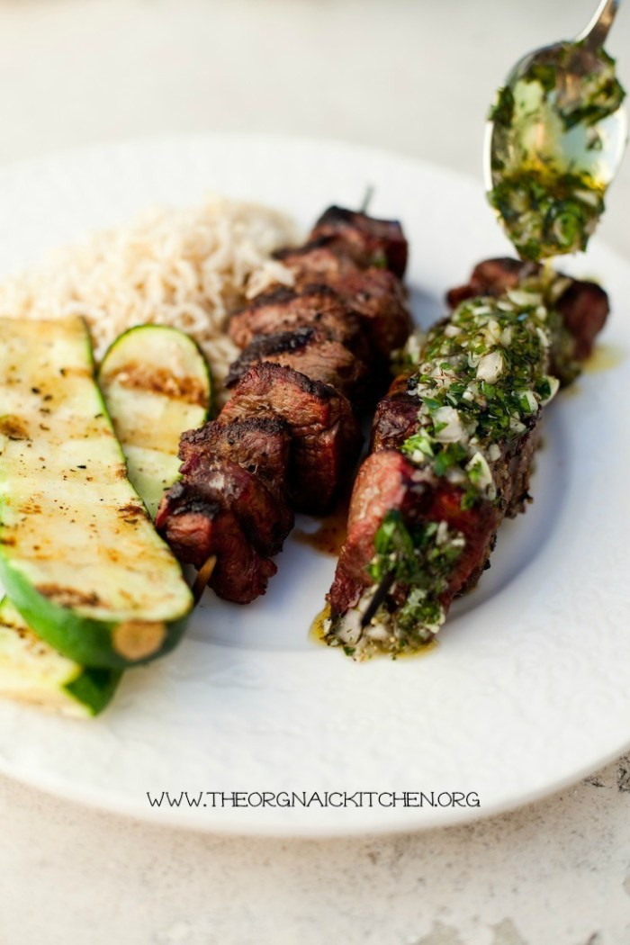 A white plate with steak kabobs, and two pieces of Simple Grilled Zucchini being drizzled with Chimichurri sauce
