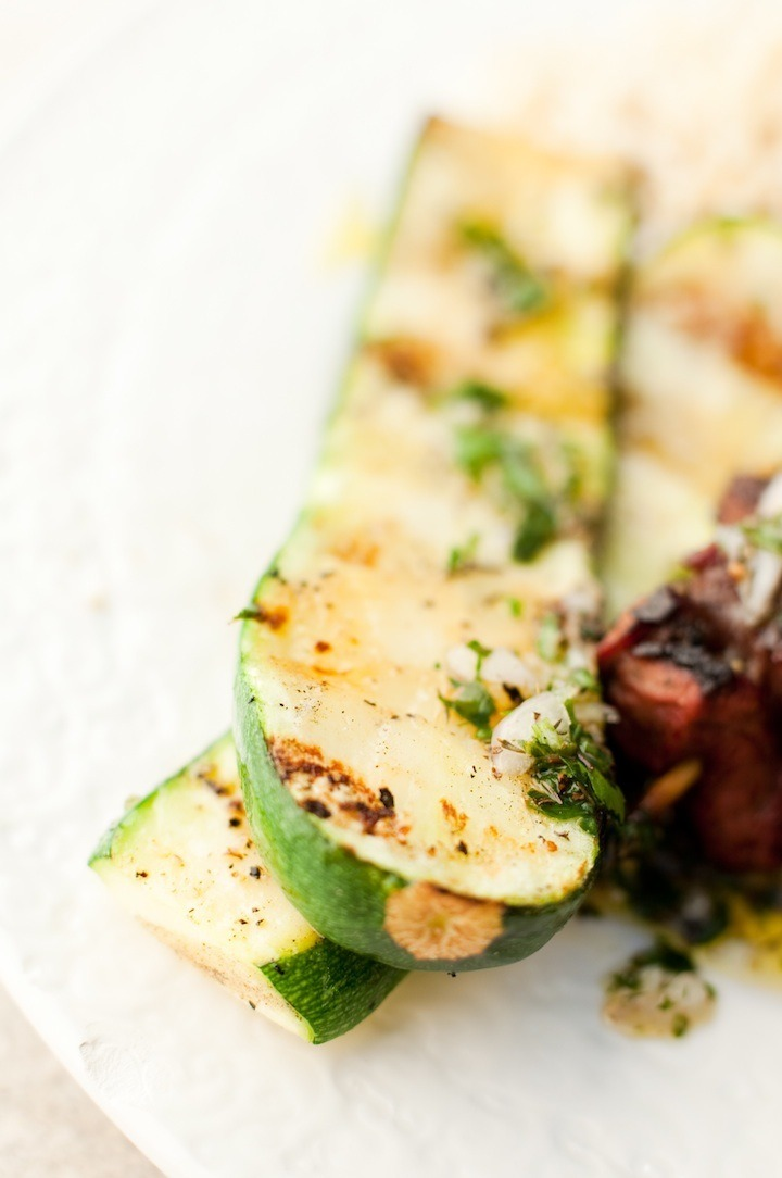 Simple Grilled Zucchini garnished with chimichurri on white plate