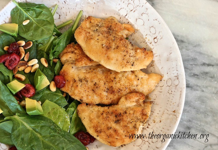 Three golden Easy Chicken Tenders in a white dish with spinach leaves