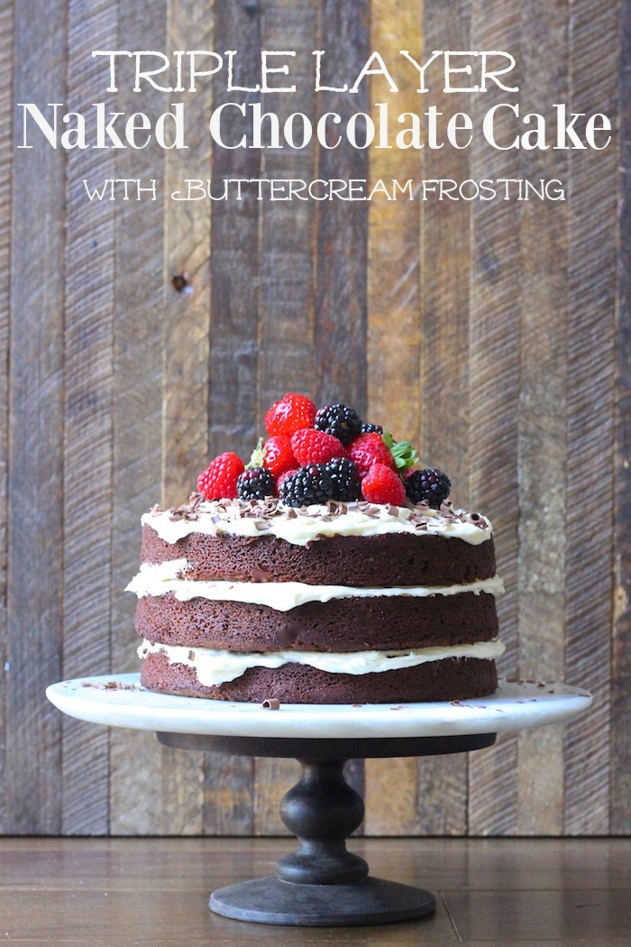 A triple layer Naked Chocolate Cake with Buttercream Frosting topped with berries on a cake plate in front of a wooden backdrop