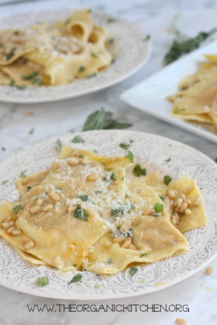 Handmade Butternut Squash Ravioli with Sage Browned Butter on white plates with grey trim on white and grey marble surface