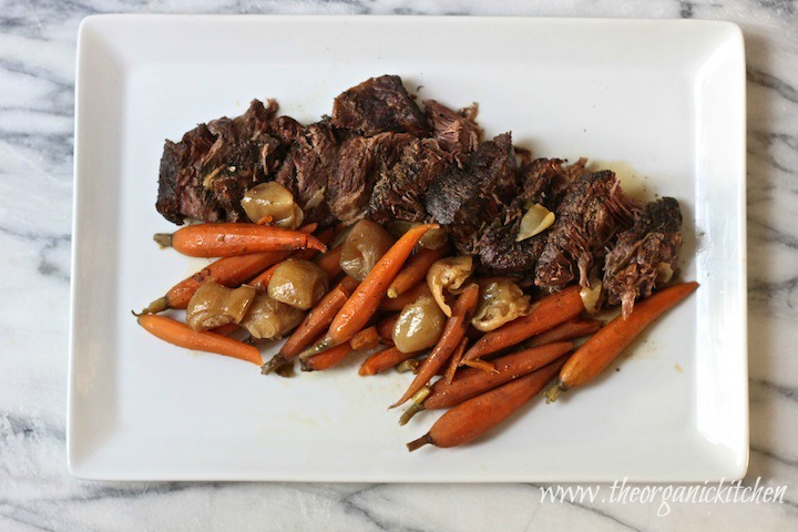 Slow Cooker Pot Roast with Shallots and Baby Carrots on white platter set on grey and white marble surface
