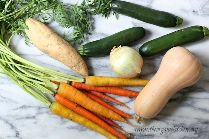 Butternut squash, zucchini, sweet potato, onion and carrots on a marble board for Roasted Vegetable Soup!