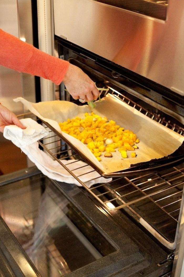 Une casserole de courge musquée coupée sur une plaque à pâtisserie à rebords est mise à rôtir pour les pâtes Farfalle à la courge musquée rôtie de www.theorganickitchen.org