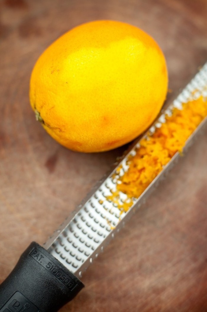 A microplane with orange zest in it next to an orange on a cutting board, Orange Cranberry Cake