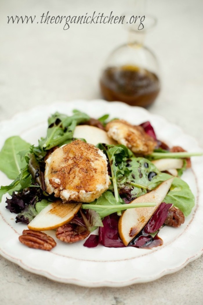 Greens with Warm Breaded Goat Cheese and Fig Balsamic on white plate with scalloped edges