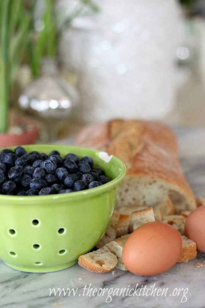 A bowl of blueberries, eggs, and French bread on marble surface. Heavenly Blueberry Bread Pudding From The Organic Kitchen