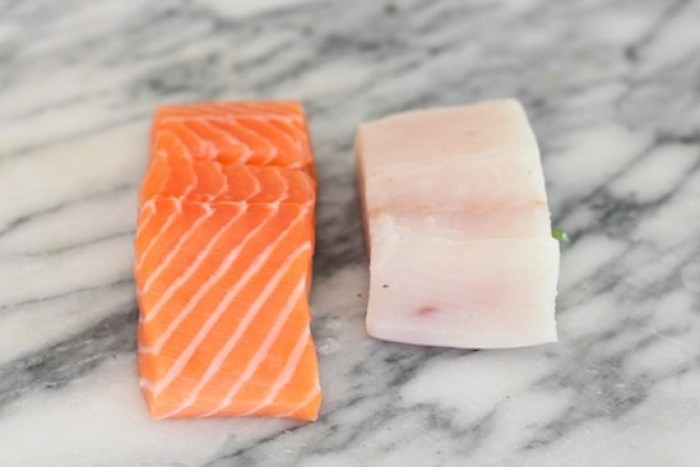 Raw salmon and halibut on marble surface in preparation for making Fresh Fish Tacos