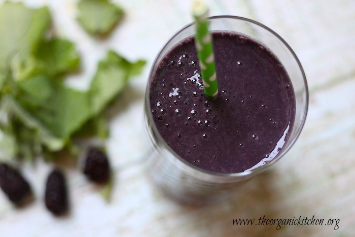An aerial view of Blackberry and Baby Kale Breakfast Smoothie in a glass with green straw