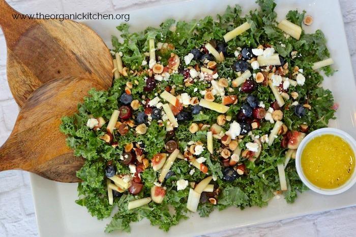 Kale Salad with Citrus Vinaigrette on white platter with wood salad tongs and dosh of citrus vinaigrette