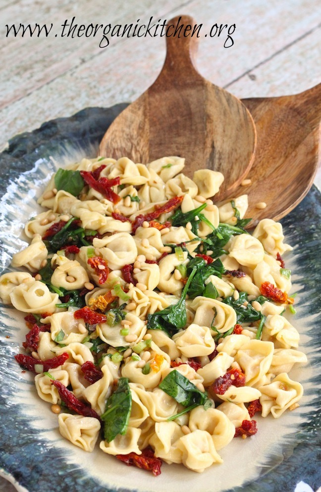 Three Cheese Tortellini with Spinach and Sun Dried Tomatoes on blue platter with wooden serving spoons