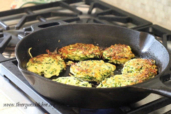 Zucchini Fritters with Lemon Ricotta (with Gluten Free Option) cooking in a cast iron skillet on the stovetop