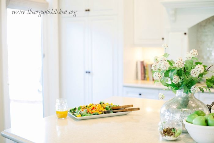 A beautiful white kitchen with a platter of Greens with Mango and Citrus Vinaigrette set on the counter