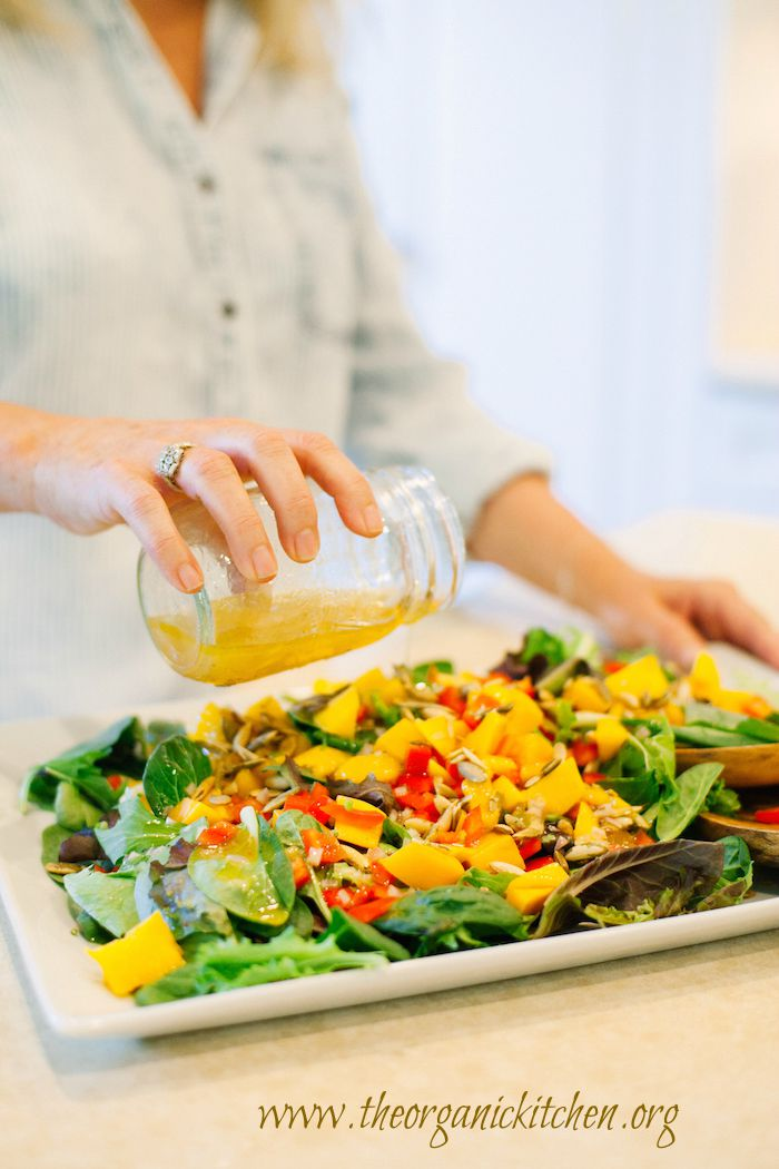A woman pouring salad dressing on  a platter of Greens with Mango and Citrus Vinaigrette
