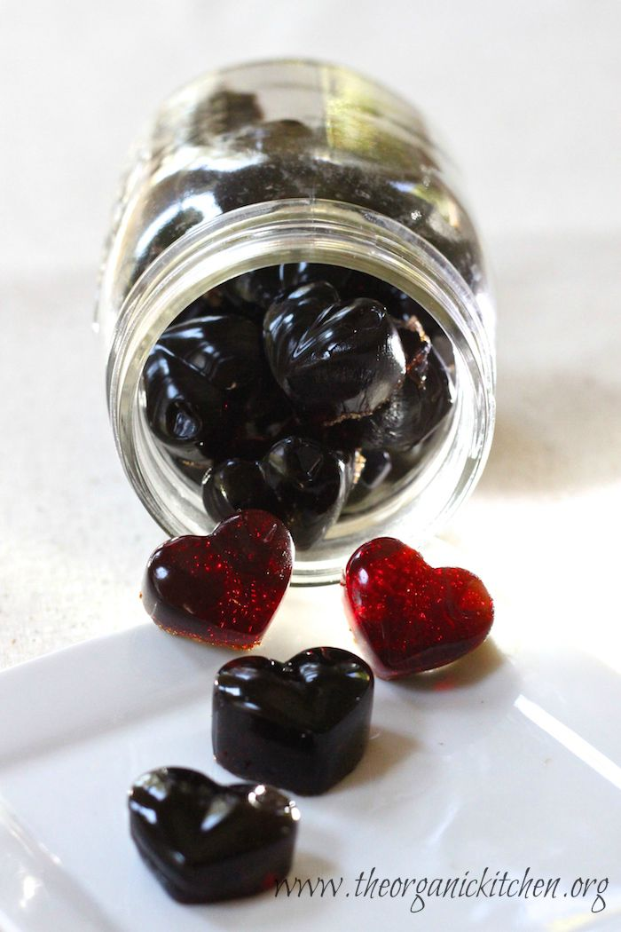 A jar lying on it's side with Pomegranate Gelatin Gummies spilling out onto a white background